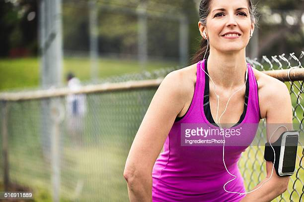 Portrait of smiling woman in 40s doing stretching during workout