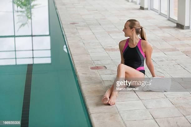 Portrait de femme souriante en maillot de bain assis au bord de la piscine