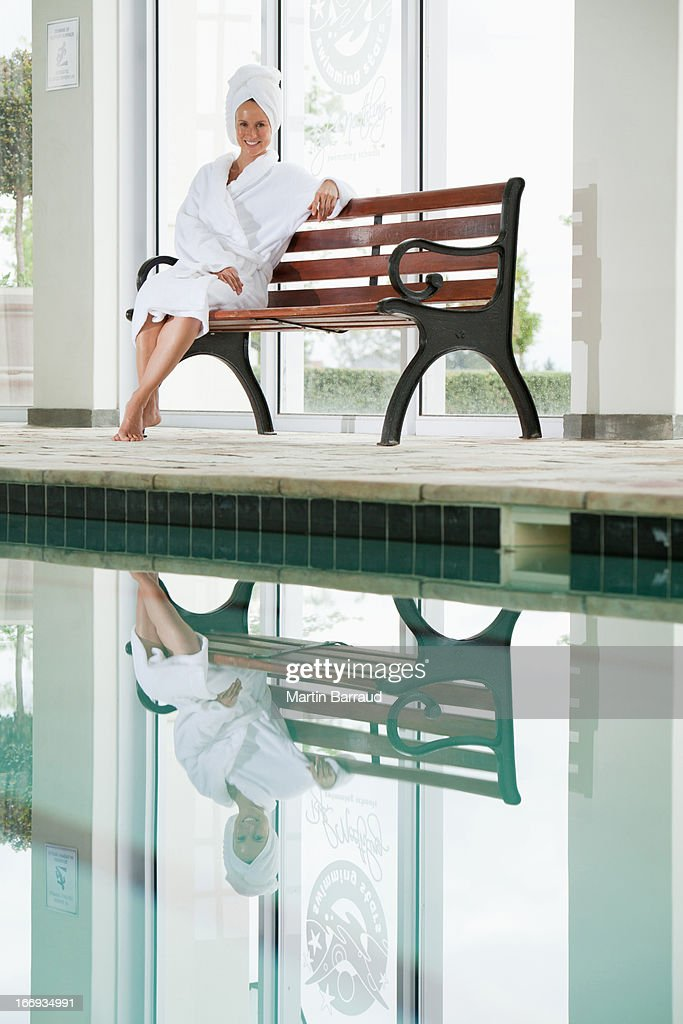 Portrait of smiling woman in bathrobe sitting on bench poolside at spa : Stock Photo