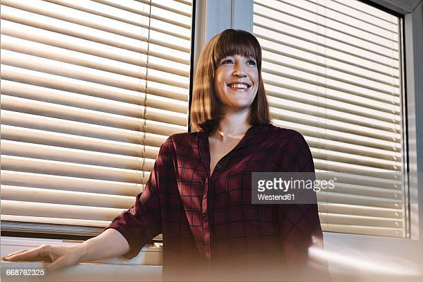 Portrait of smiling woman in front of window