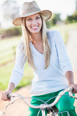 Portrait of smiling woman in straw hat riding bicycle