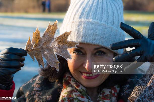 Portrait Of Smiling Woman In Warm Clothing Holding Frozen Leaf