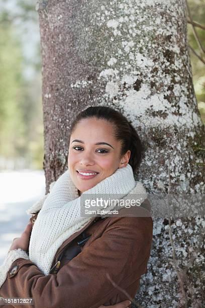 Porträt eines lächelnden Frau schiefen gegen tree trunk