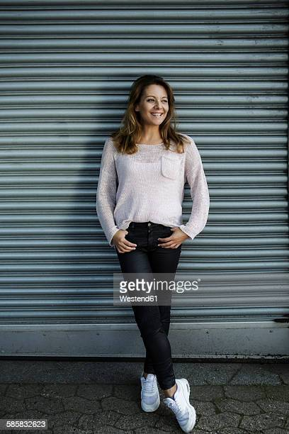 Portrait of smiling woman leaning on roller shutter