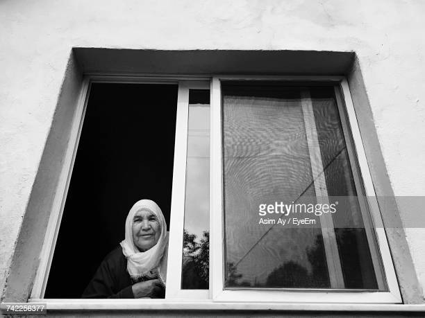 Portrait Of Smiling Woman Looking Through Window