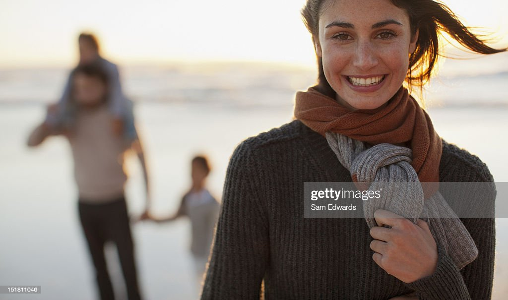 Portrait of smiling woman on beach with family in background : Stock Photo