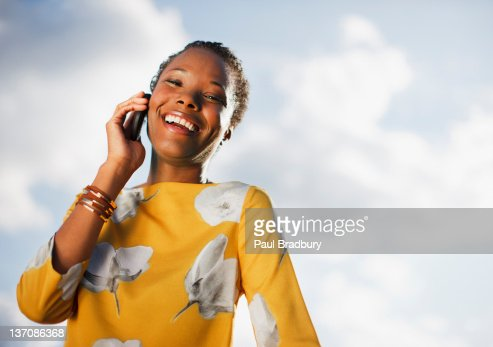 Portrait of smiling woman on cell phone under blue sky with clouds : Stock Photo
