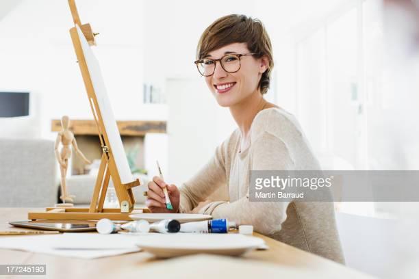 Portrait de sourire femme peinture au Chevalet de peintre sur table