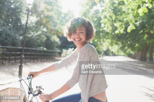 Portrait of smiling woman riding bicycle in sunny park : Stock Photo