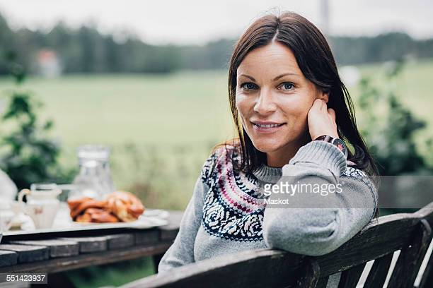Portrait of smiling woman sitting at breakfast table in organic farm