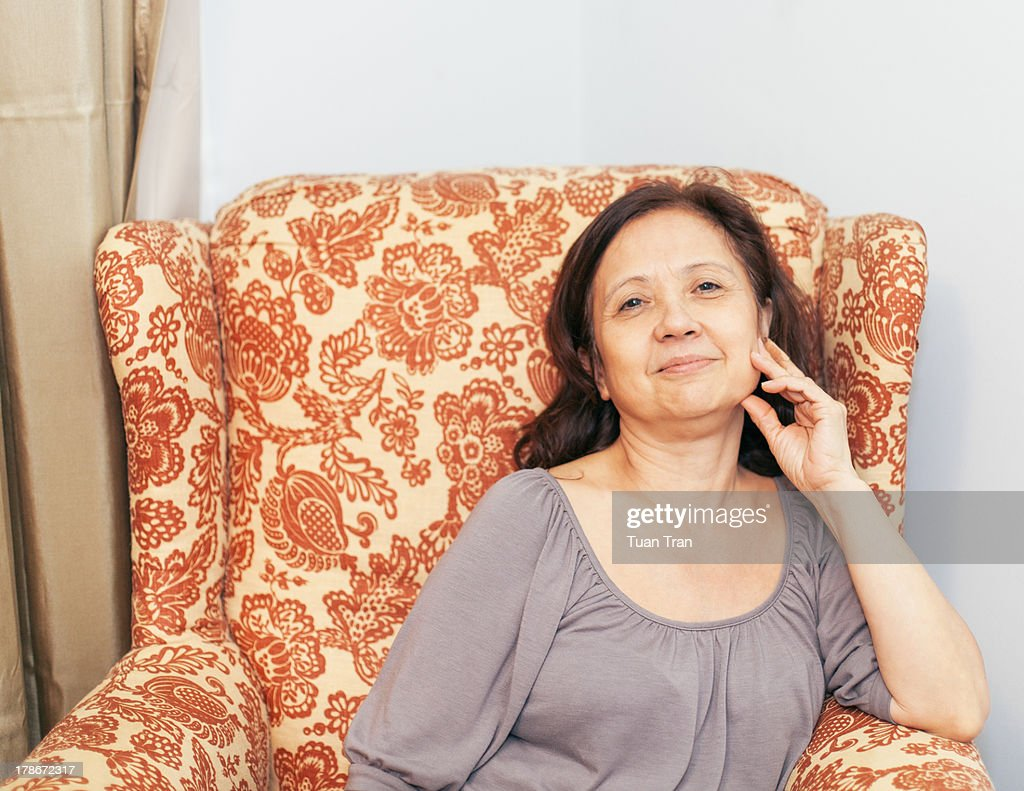 Portrait of smiling woman sitting on chair : Stock Photo