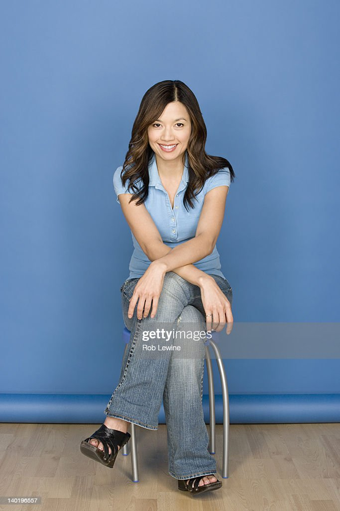 Portrait of smiling woman sitting on chair with blue background, studio shot