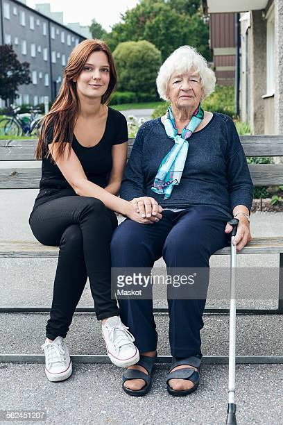 Portrait of smiling woman sitting with granddaughter on bench outdoors