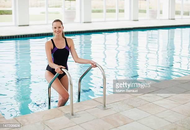 Porträt eines lächelnden Frau stehend auf Leiter im Swimmingpool