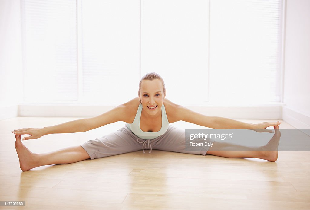 Portrait of smiling woman stretching with legs apart : Stock Photo