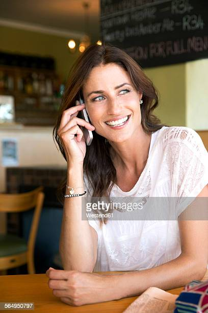 Portrait of smiling woman telephoning with smartphone in a cafe