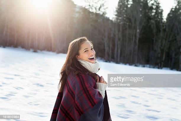 Portrait of smiling woman walking in snowy field