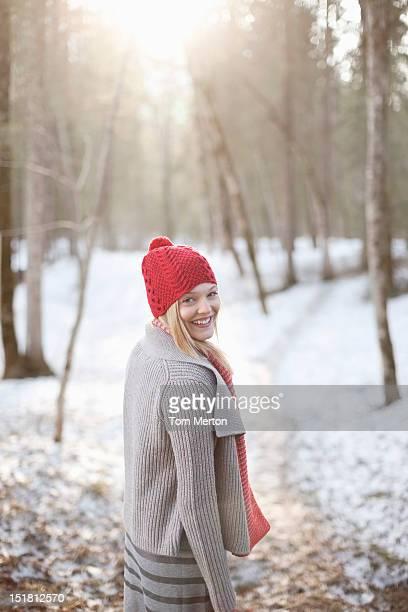 Portrait de sourire Femme marchant dans la neige bois