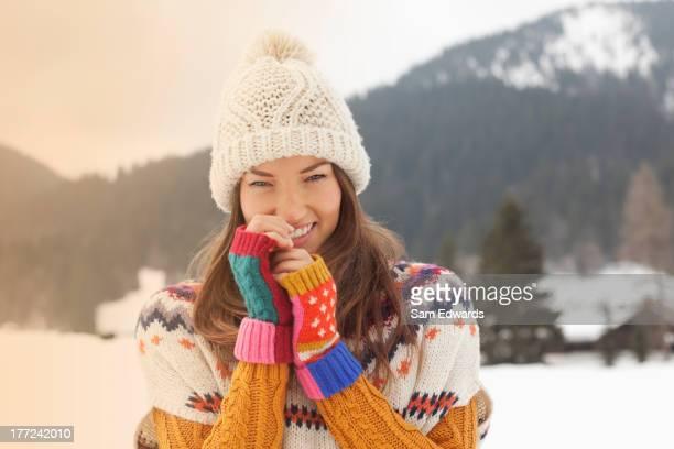 Portrait de femme souriante portant Chapeau en tricot champ de neige