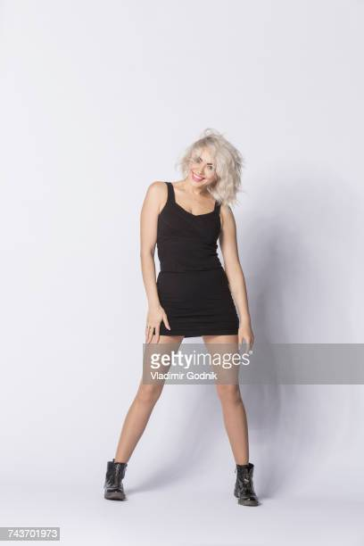 Portrait of smiling woman wearing mini dress posing against white background