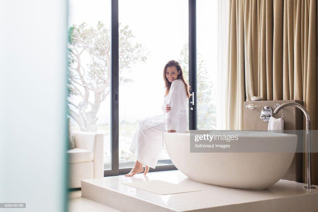 Portrait of smiling woman wearing white bathrobe, sitting on edge of bathtub in bathroom