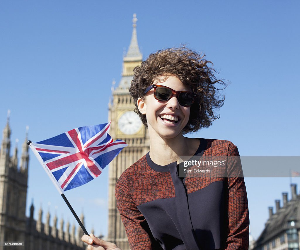 Portrait of smiling woman with British flag in front of Big Ben clocktower : Stock Photo