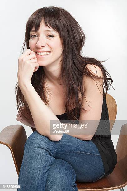 Portrait of smiling woman with dark long hair sitting on a chair