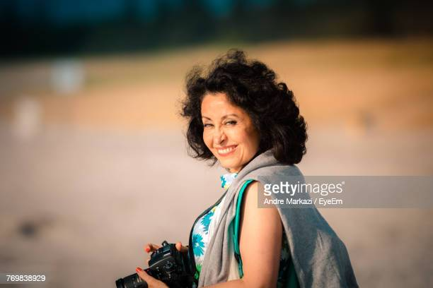 Portrait Of Smiling Woman With Digital Camera Standing Outdoors