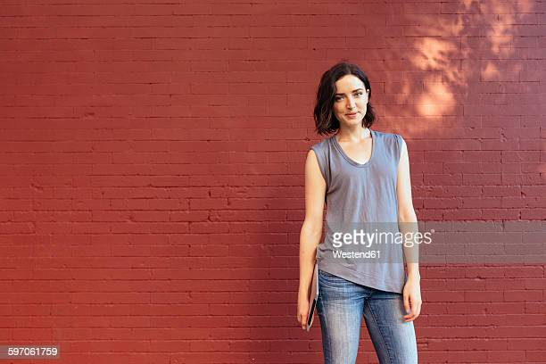 Portrait of smiling woman with digital tablet standing in front of red brick wall