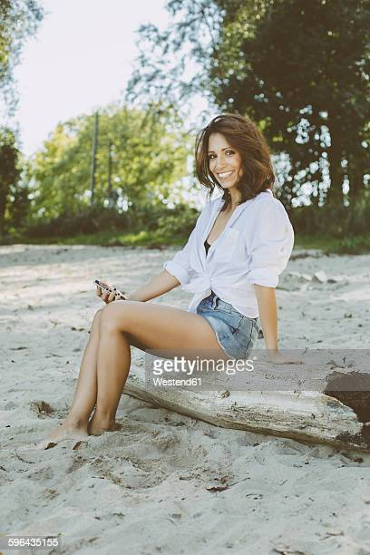 Portrait of smiling woman with smartphone sitting on dead wood on the beach