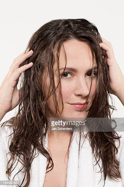 Portrait of smiling woman with wet hair, studio shot