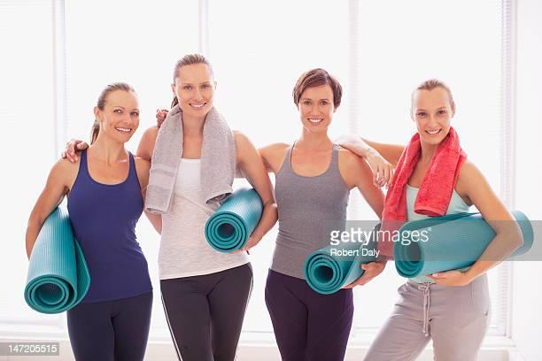 Portrait of smiling women holding yoga mats