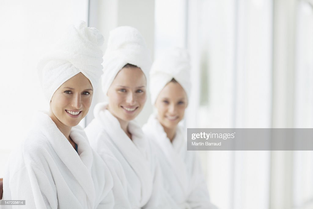 Portrait of smiling women in bathrobes and hair wrapped in towels at spa : Stock Photo