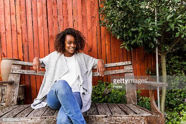 Portrait of smiling women sitting on bench in yard