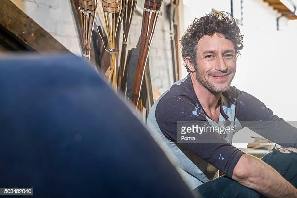 Portrait of smiling worker sitting in workshop