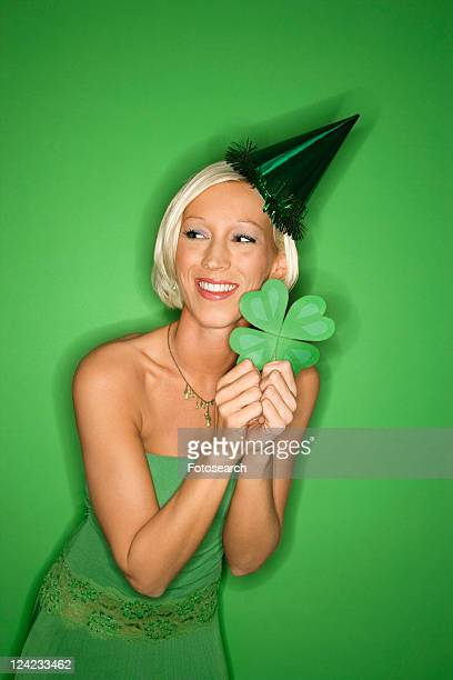 Portrait of smiling young adult Caucasian blond woman on green background wearing party hat and holding shamrock for Saint Patricks Day celebration.