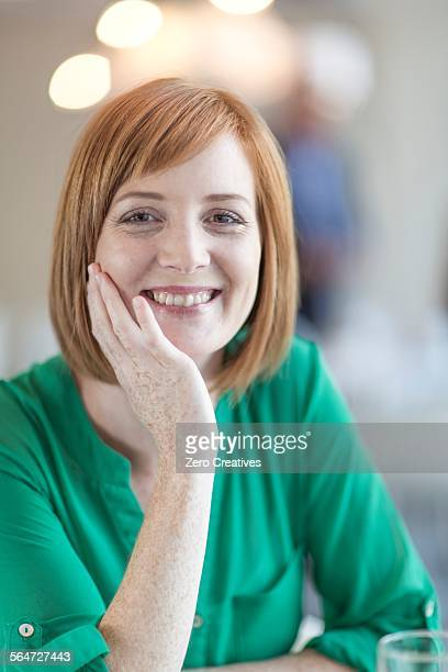 Portrait of smiling young businesswoman with red hair