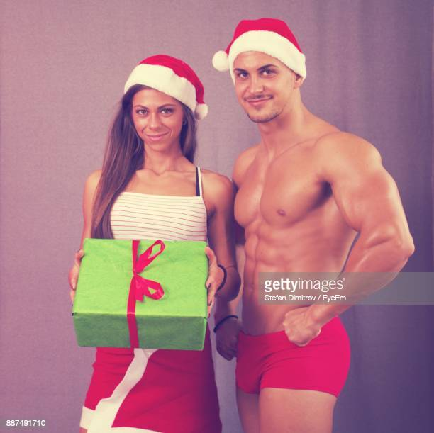 Portrait Of Smiling Young Couple Standing Against Wall During Christmas