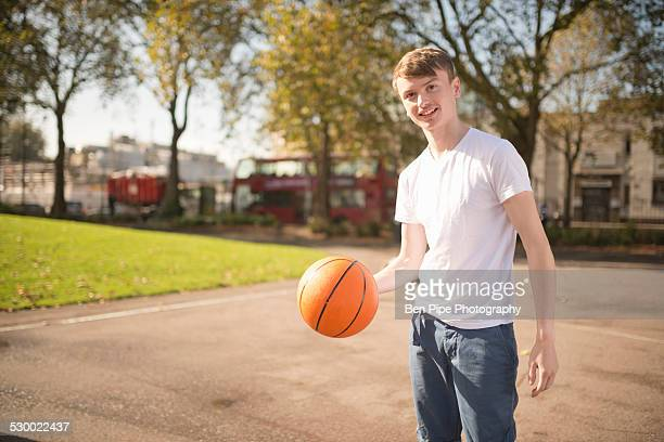 Portrait of smiling young male basketball player holding basketball