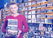 Portrait of smiling young male holding stack of DVDs in shop indoors