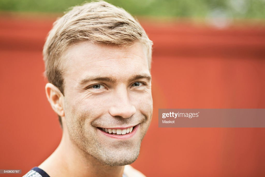 Portrait of smiling young man against wall