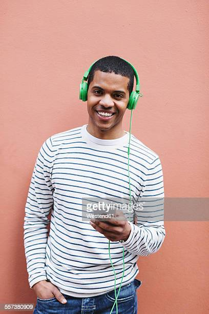 Portrait of smiling young man hearing music with green headphones