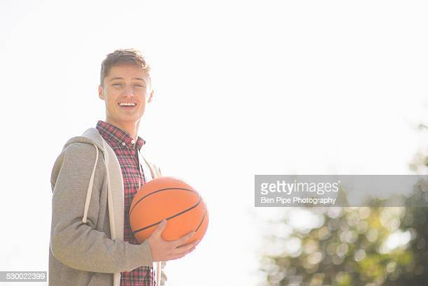 Portrait of smiling young man holding basketball