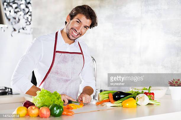 Portrait of smiling young man preparing food