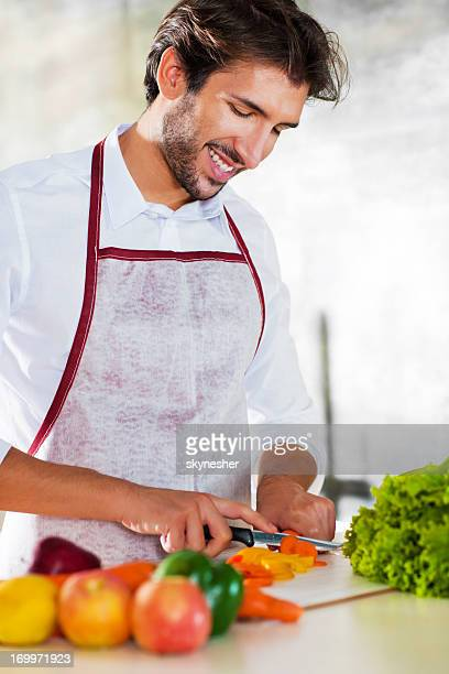 Portrait of smiling young man preparing food.