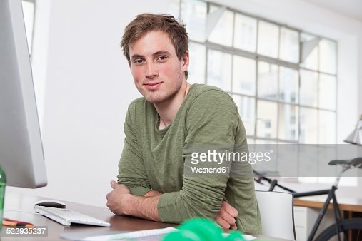 Portrait of smiling young man sitting at his desk in the office