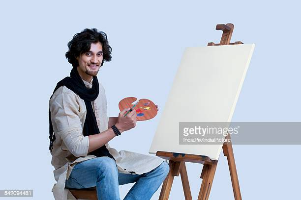 Portrait of smiling young man sitting next to easel against colored background