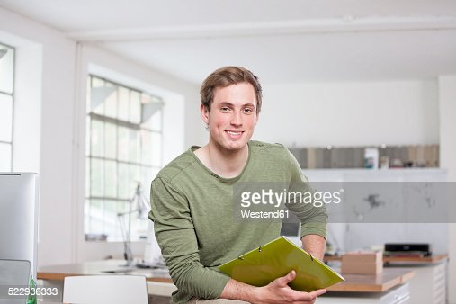 Portrait of smiling young man sitting on his desk in the office