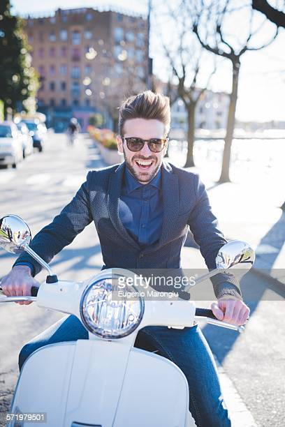 Portrait of smiling young man sitting on moped at roadside