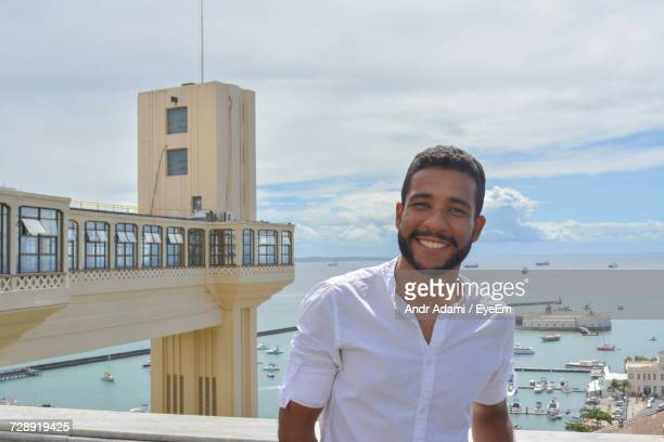 Portrait Of Smiling Young Man Standing On Pier Against Sky On Sunny Day